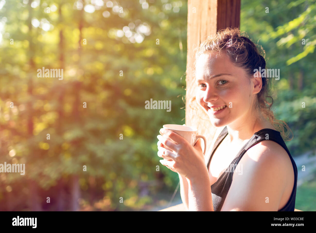 Wom standing on porch of house in morning wooden cabin cottage drinking coffee or tea with sunrise light - Stock Image