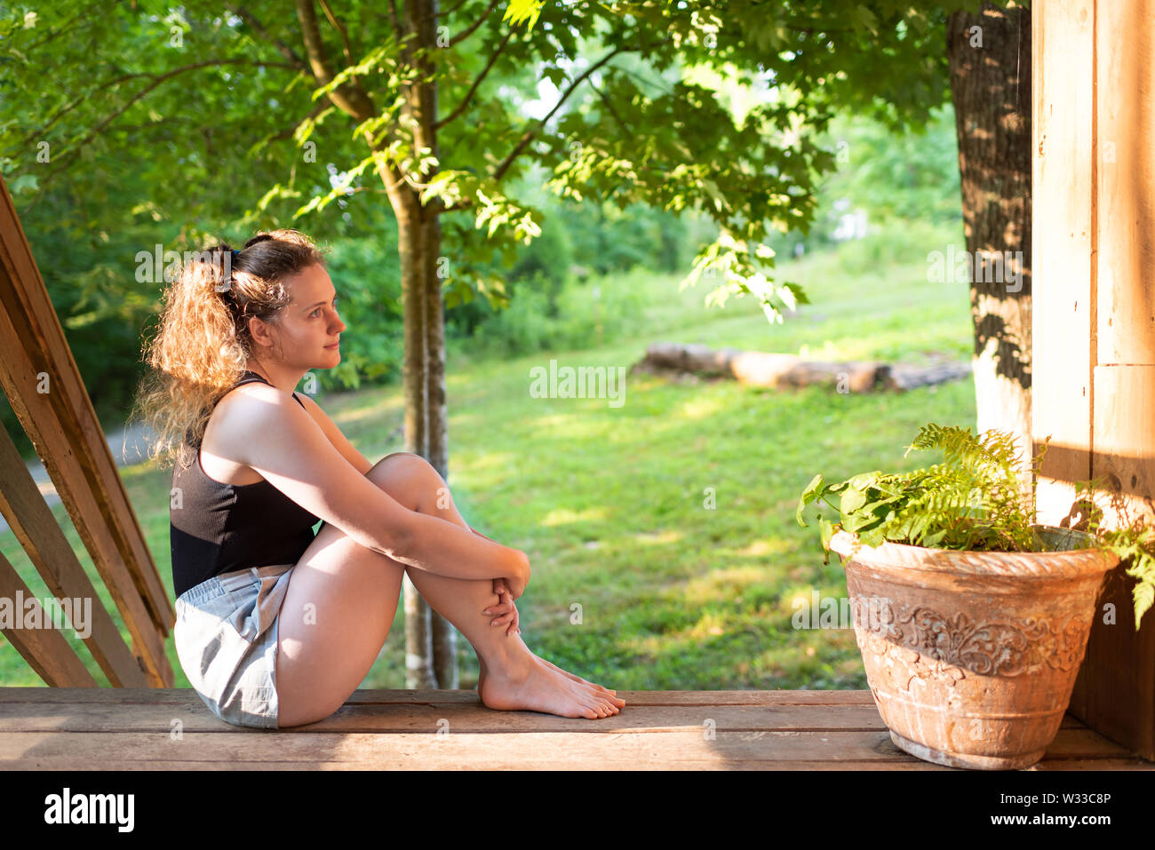 Spring house porch with happy woman sitting on steps of house in front or back yard morning wooden cabin cottage - Stock Image