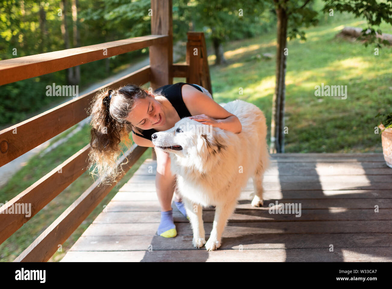 Young woman petting one happy white great pyrenees dogs outside at home porch of log cabin - Stock Image
