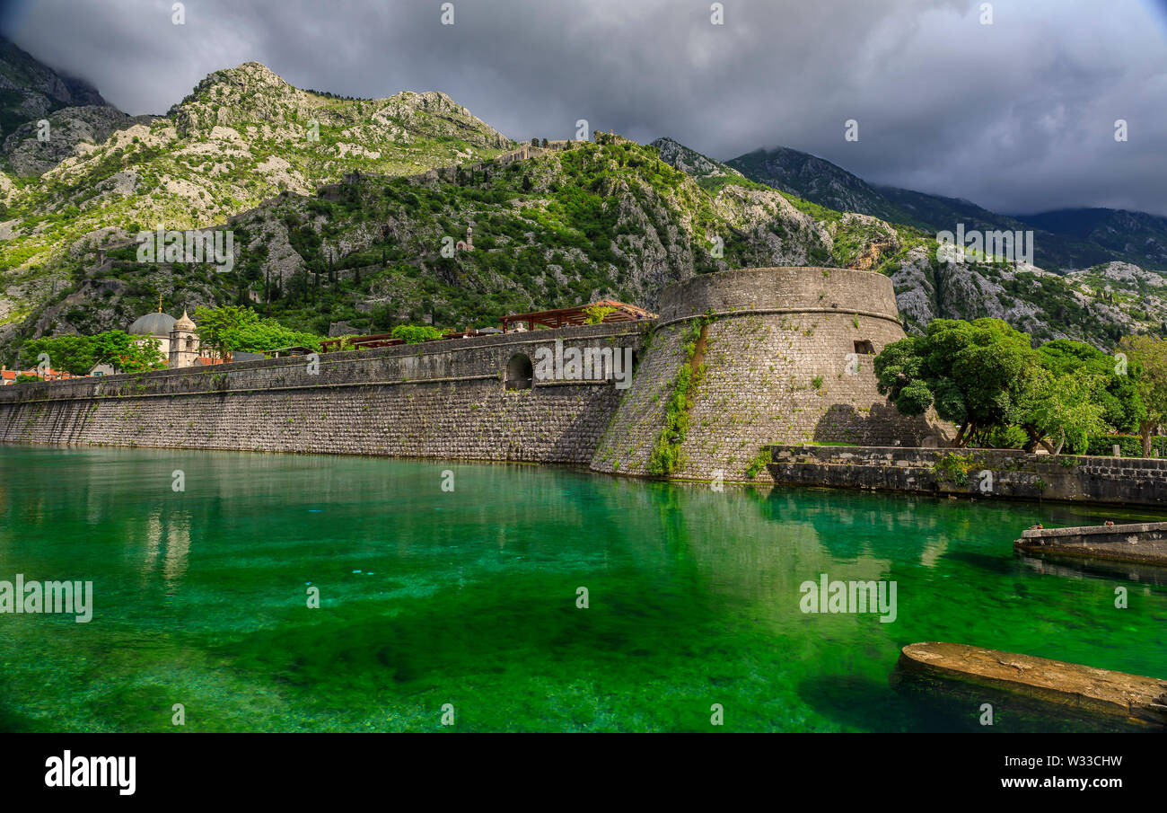 Emerald green waters of Kotor Bay or Boka Kotorska, mountains and the ancient stone city wall of Kotor old town former Venetian fortress in Montenegro - Stock Image