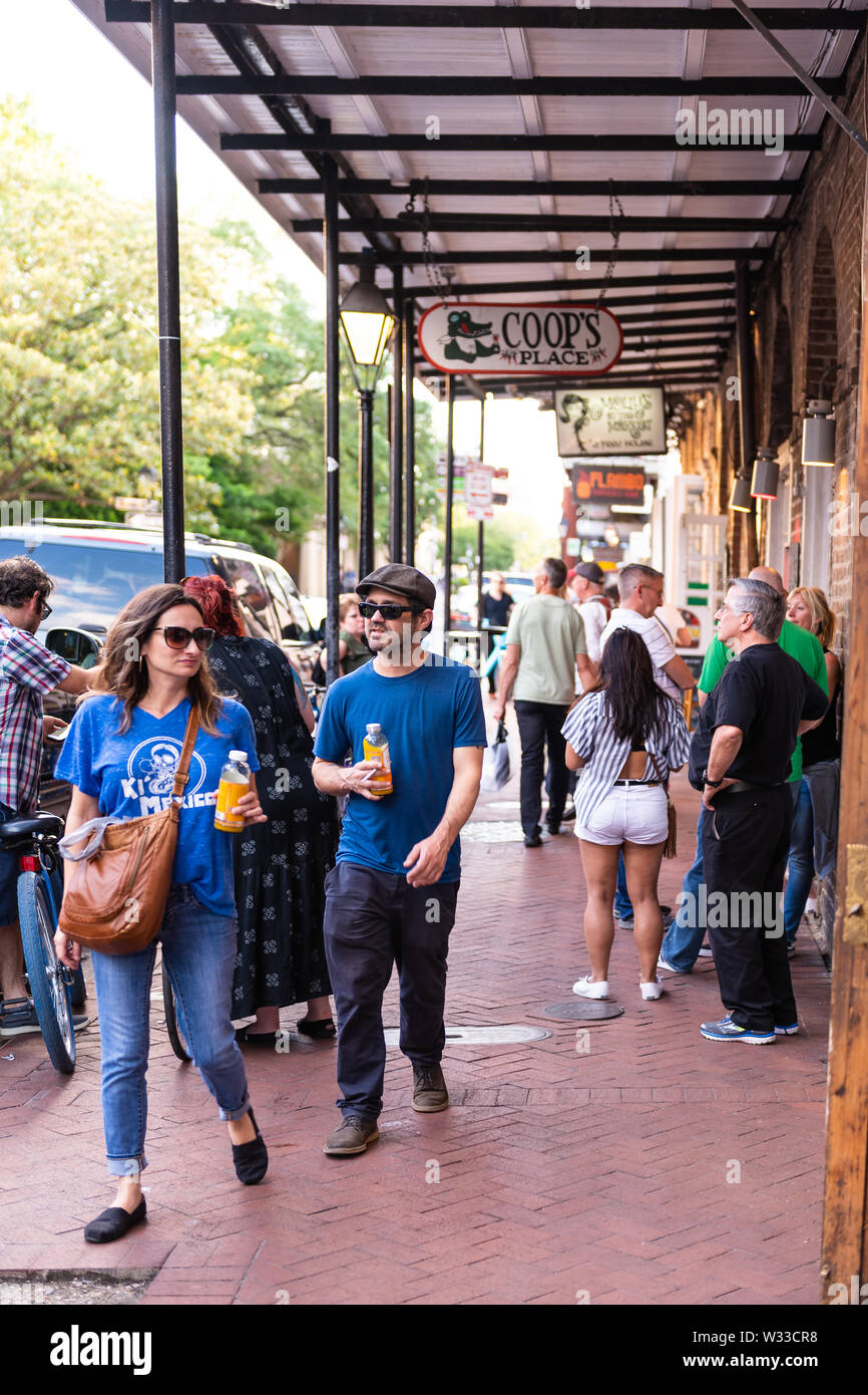 New Orleans, USA - April 22, 2018: People walking on Decatur street sidewalk in French quarter by Coop's Place restaurant in evening in Louisiana famo - Stock Image