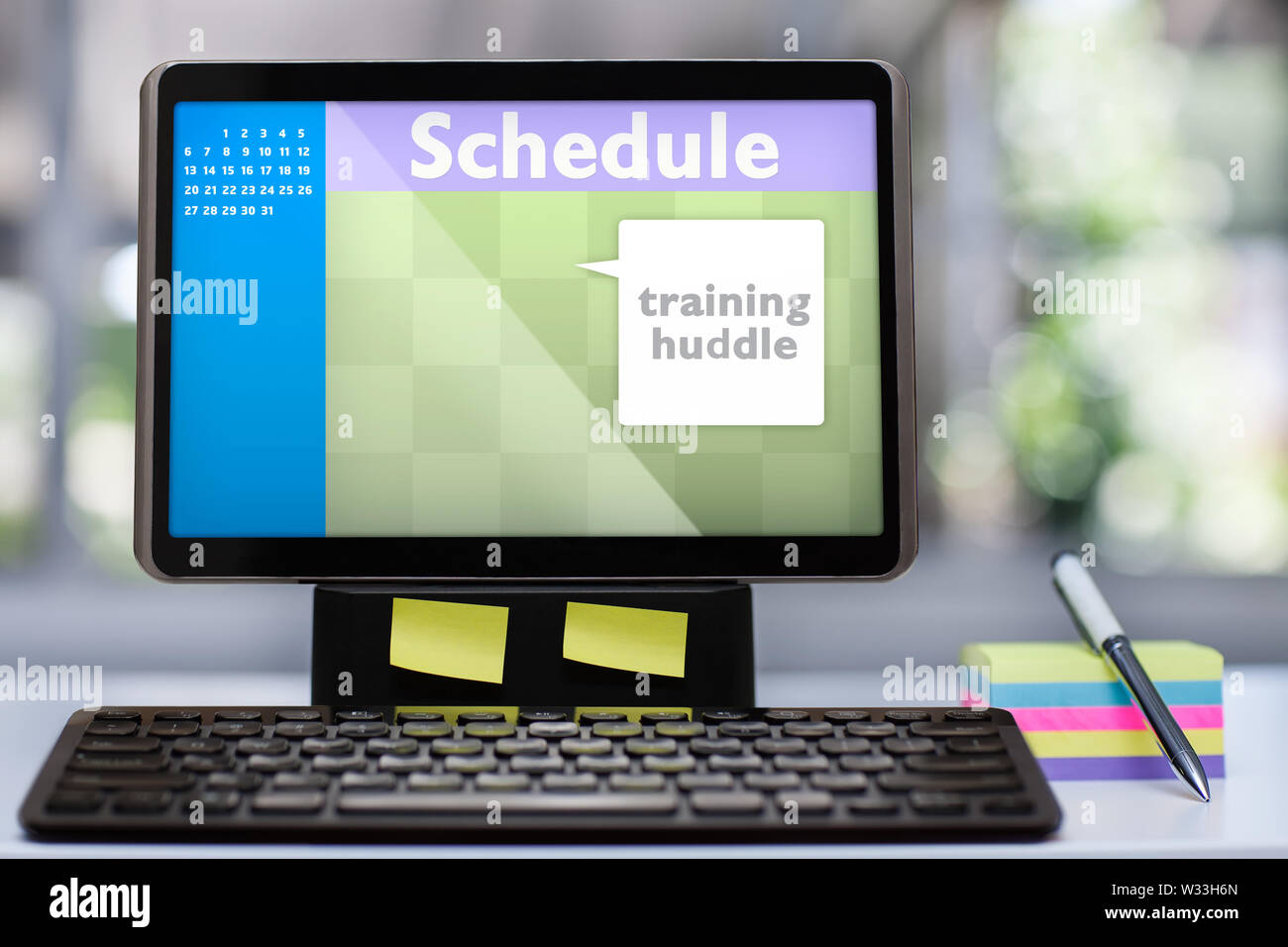 A tablet computer workstation with mockup scheduling software application on a office desk with colorful sticky notes, a pen and wireless keyboard. - Stock Image