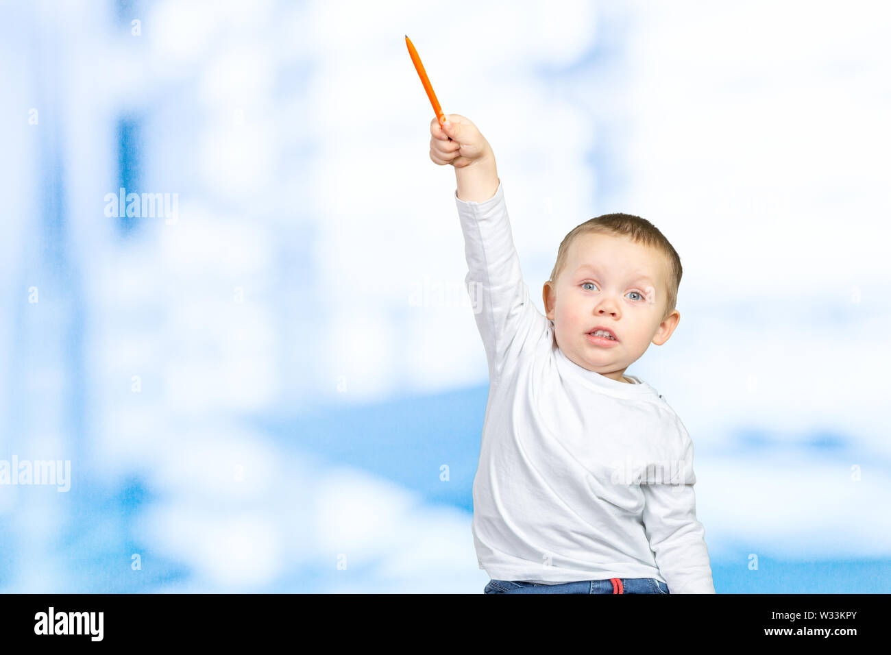 Cheerful little boy pointing up - Stock Image