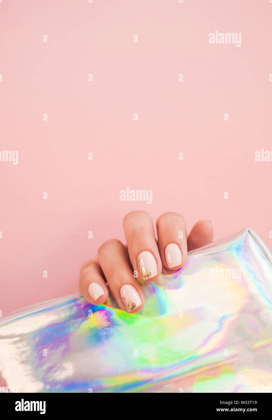 Young woman's hand with beautiful manicure on beige background holding metallic holographic paper. - Stock Image