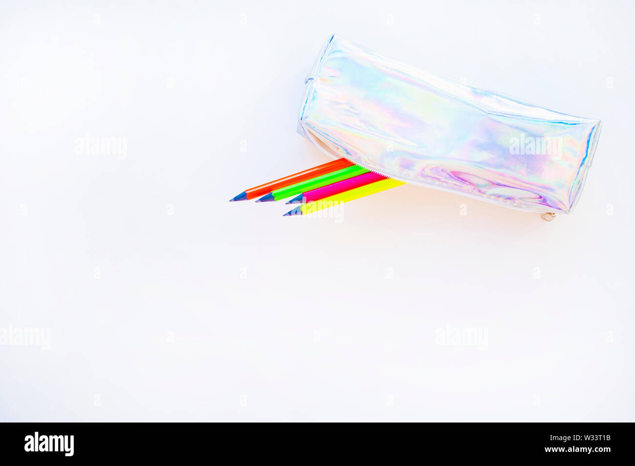 Colorful paper, neon pencils and holographic pencil case on beige background with copyspace. Flat lay style. Back to school concept. - Stock Image