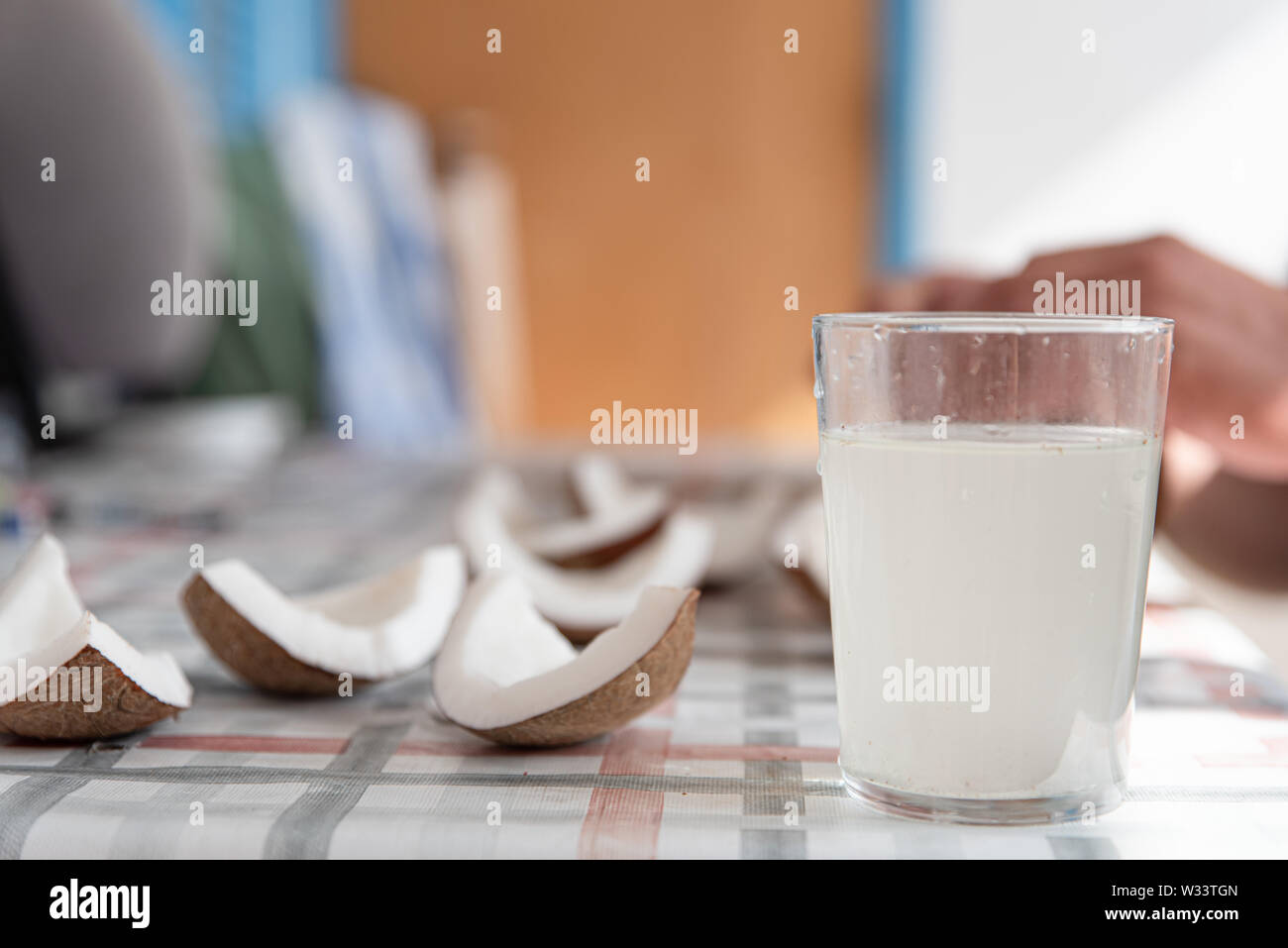 Coconut water and fresh pieces coconut on the table. Exotic food form Dominican Republic. Stock Photo