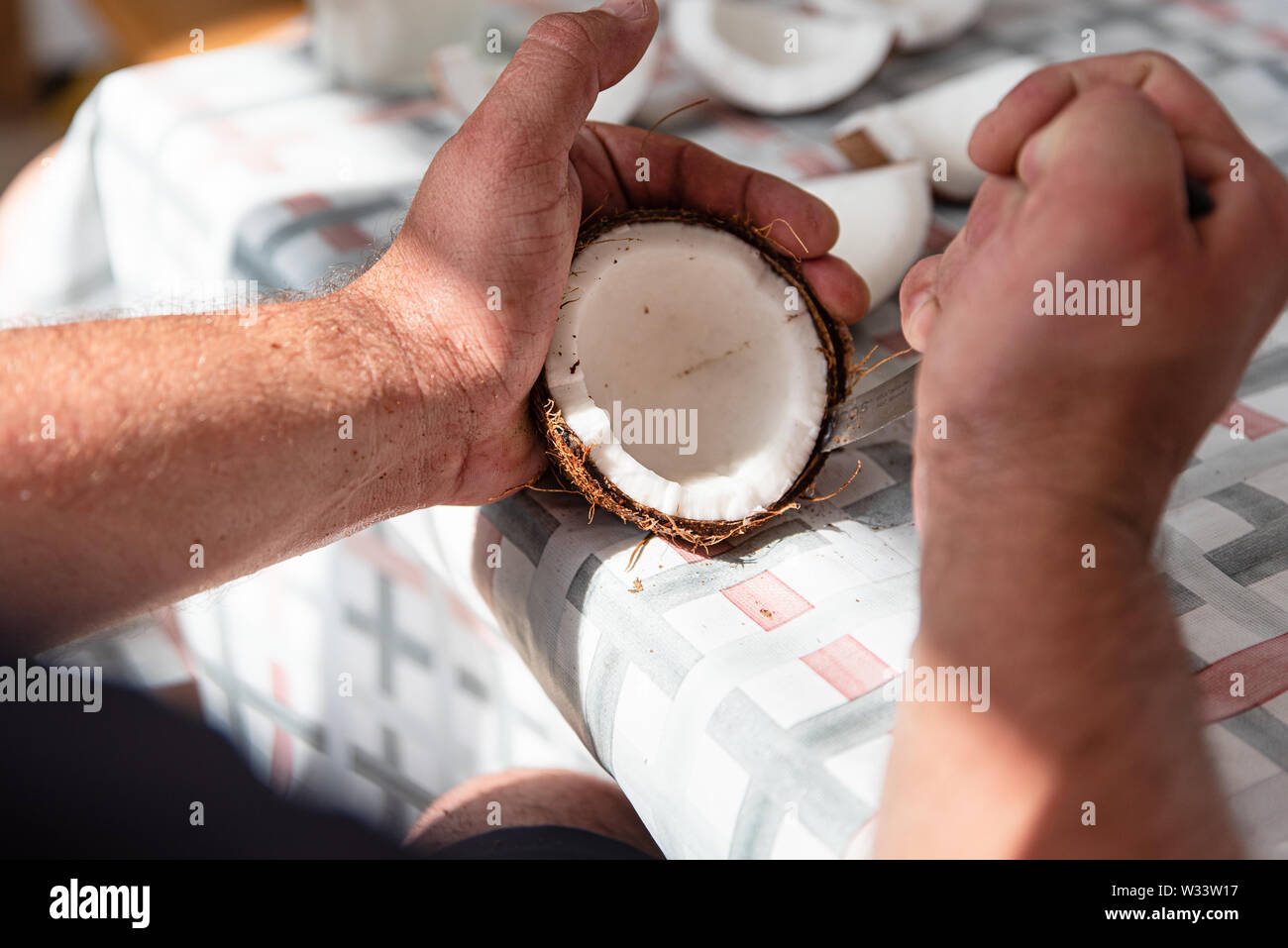 Man cut fresh coconut into pieces, process close up. Exotic food at home Stock Photo