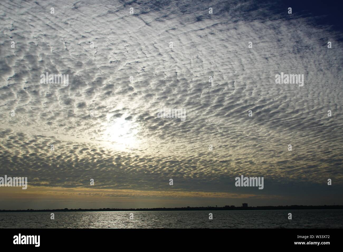 Dramatic Morning Sky with a Cluster of small dense Clouds over Water Stock Photo