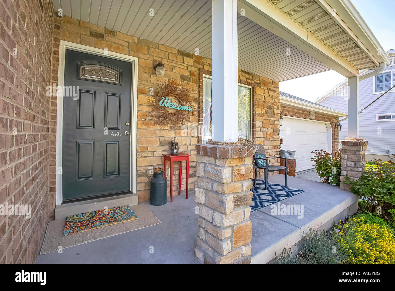 Gl paned front door and stone brick exterior wall at the ... on front of house storage, front of house trees, front of house landscaping, front of house awards, front of house signs, front of house decor, front of house lighting,