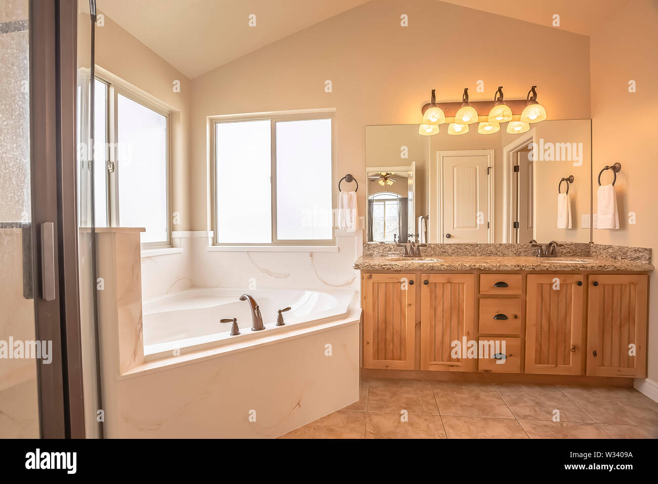 Built In Bathtub At The Corner Of A Home Bathroom With Tile Floor And Beige Wall Sliding Windows And A Vanity With Double Sink Can Also Be Seen Insid Stock Photo