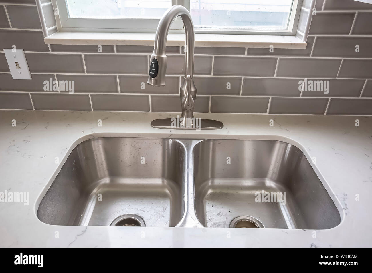 Double Bowl Stainless Steel Sink Undermounted On The White Kitchen Countertop Tiled Wall And Window Can Be Seen Behind The Faucet Stock Photo Alamy