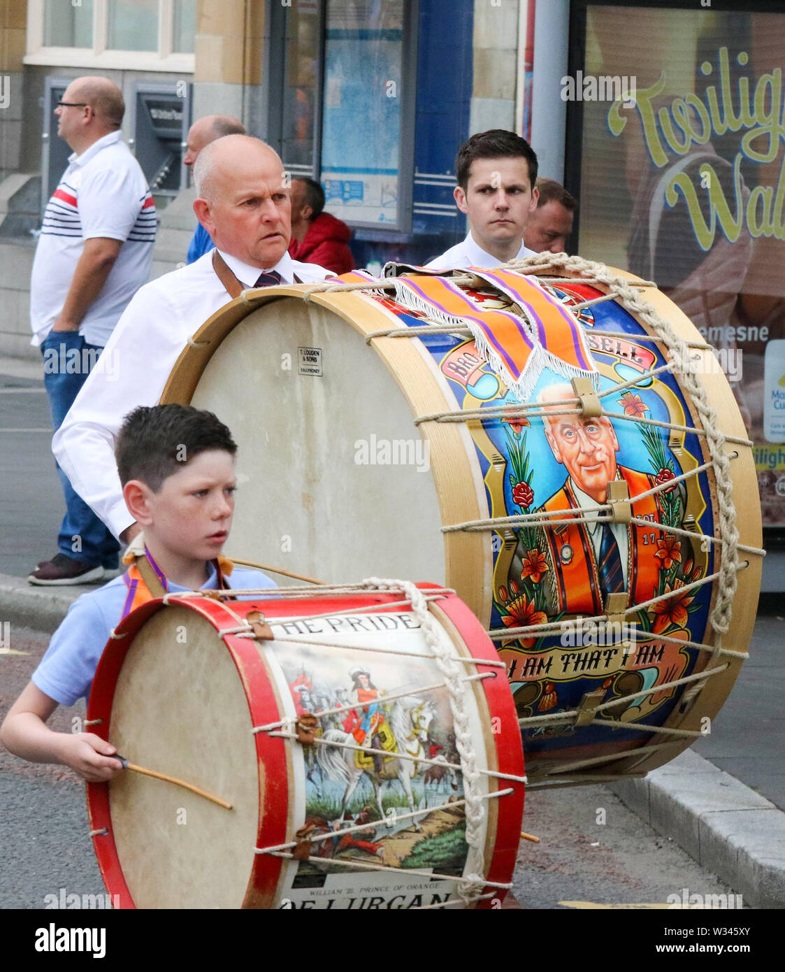 Lurgan, County Armagh, Northern Ireland.12 July 2019. The Twelfth of July is marked by Orange Order parades across Northern Ireland. Lurgan District left their headquarters at Brownlow House before parading up the town to the war memorial and then headed to the town of Tandragee for the main County Armagh demonstration. The parades across Northern Ireland mark the victory of William of Orange over James at the Battle of the Boyne in 1690. Lambeg drums being played. Credit: CAZIMB/Alamy Live News. - Stock Image