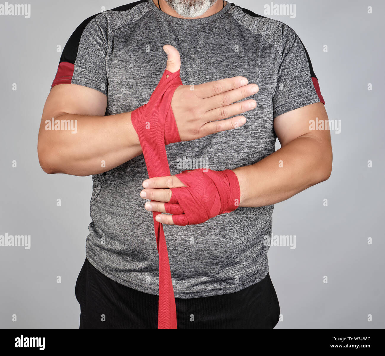 Athlete Stand In Gray Clothes And Wrap His Hands In Red Textile