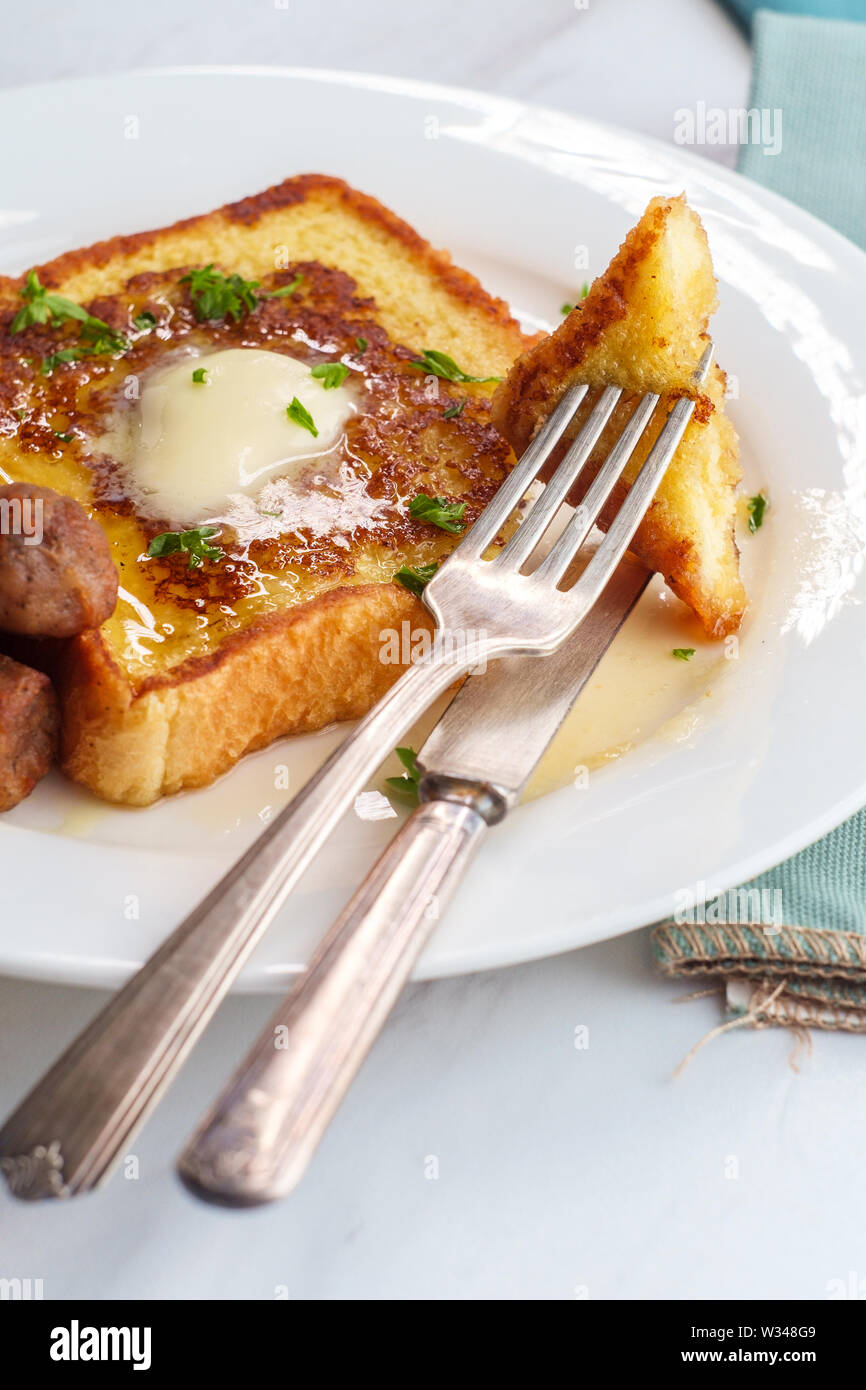 Classic American breakfast french toast with maple syrup served with side of sausage links Stock Photo