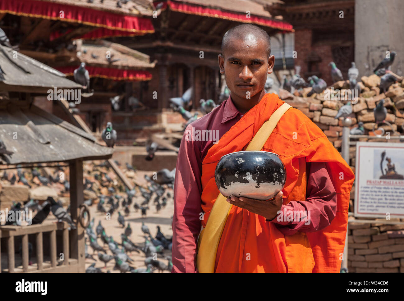 Buddhist monk in orange robes collecting donations for damaged temples in Kathmandu. - Stock Image