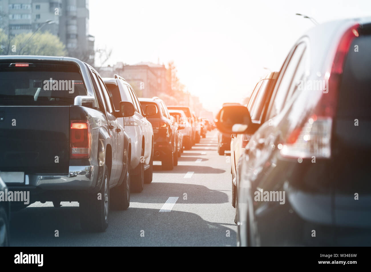 Evening traffic jam on busy city highway. Rows of car stck on road due to crush accident. Sunset metropolis rush hour scene. - Stock Image