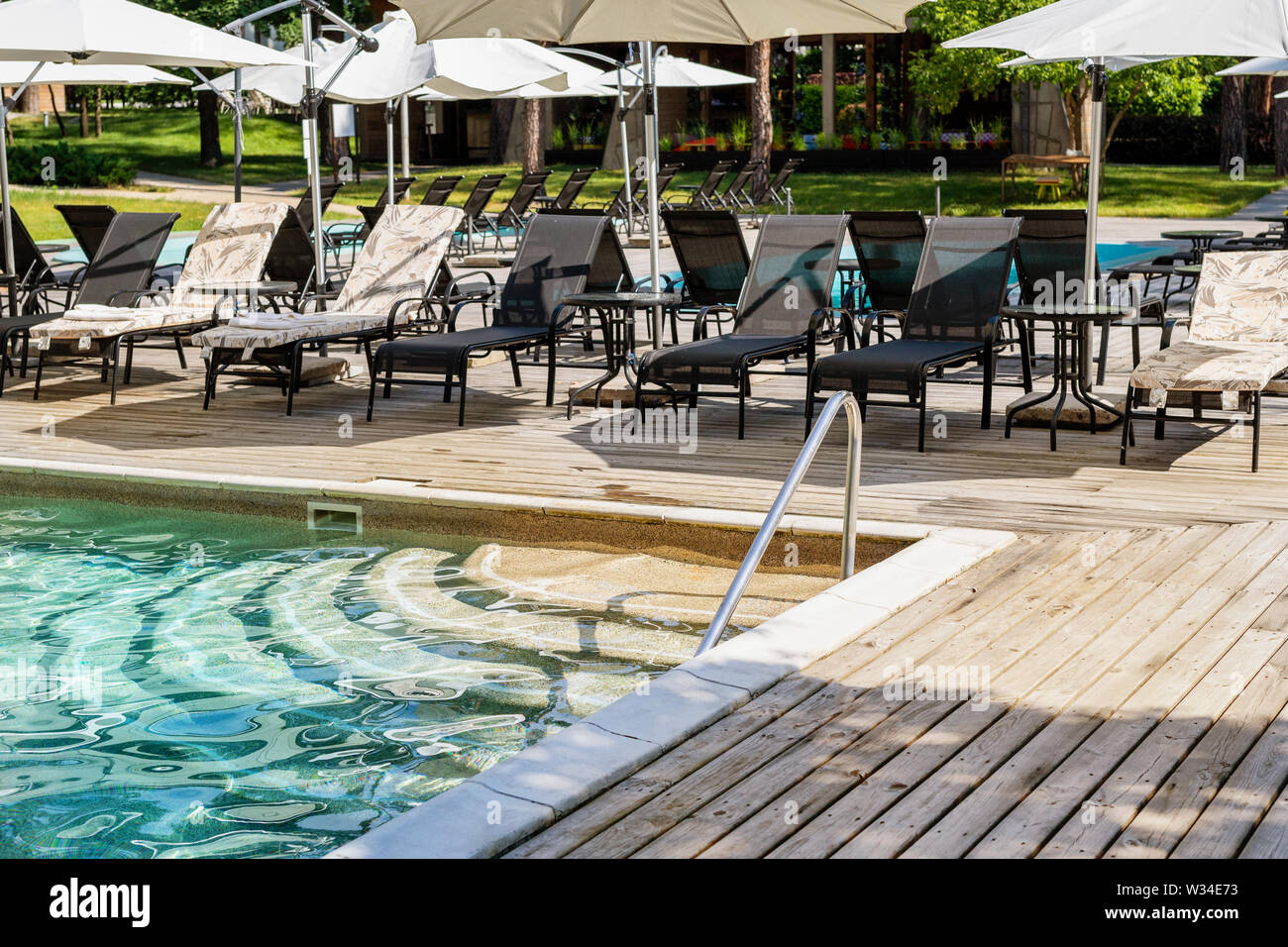 Poolside with clear blue water and loungers under umbrellas ...