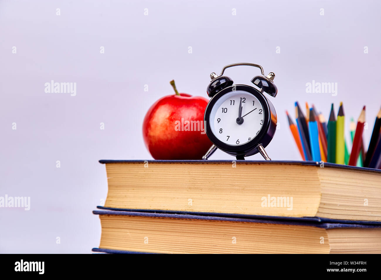 Back to school supplies. Books and red apple on green background. Still life with alarm clock. Copy space. Stock Photo