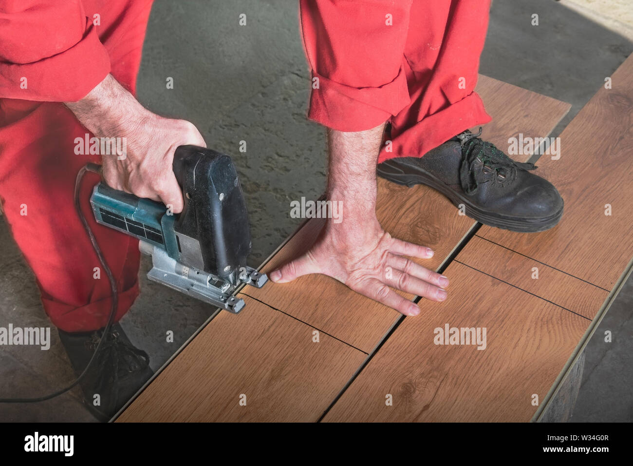 A worker in a red jumpsuit cuts a laminate with a jigsaw by marking, resting his foot on the bar. Master saws the bar with an electric saw in the work - Stock Image