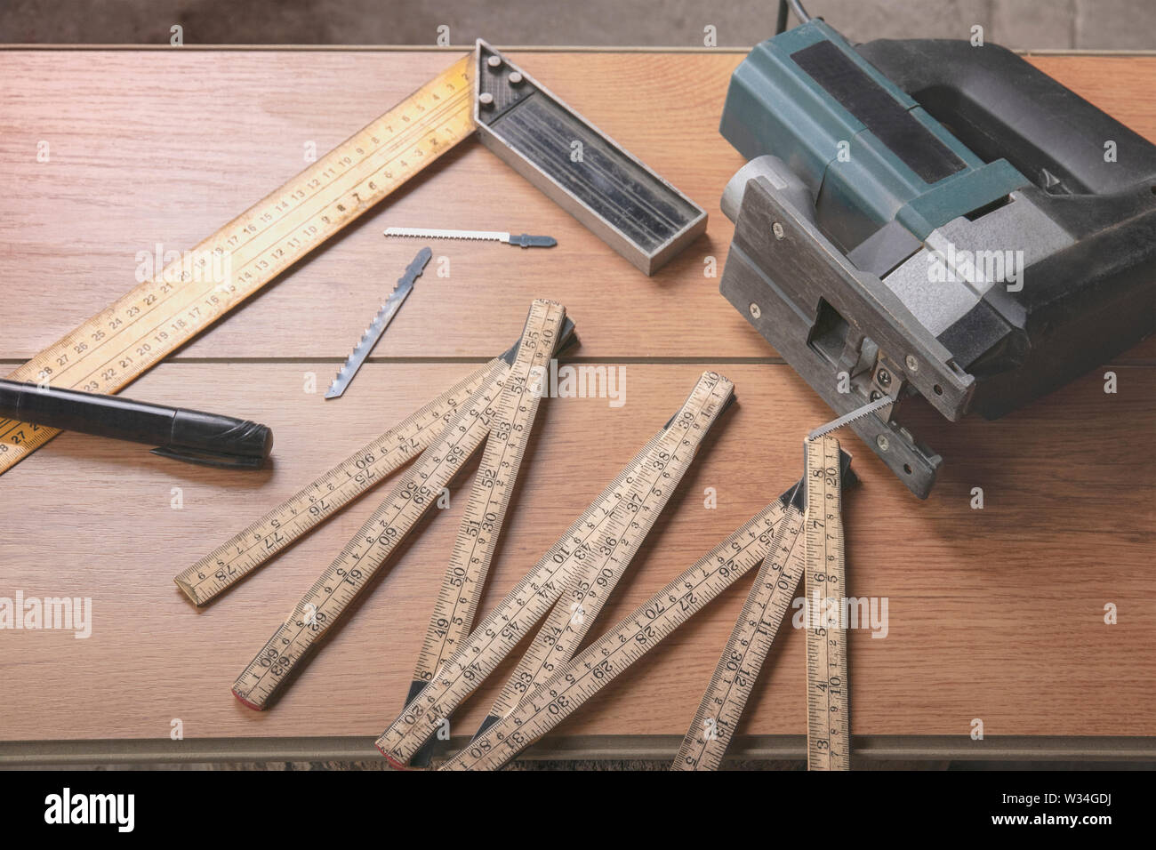 Electric jigsaw, folding ruler, square, marker for marking, replaceable files for electric saws lie on a wooden laminate. Tools carpenter and electric - Stock Image