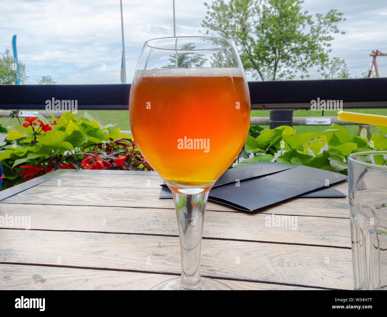 Half glass of beer on a beautiful wooden old table on the veranda of the restaurant, relax time - Stock Image