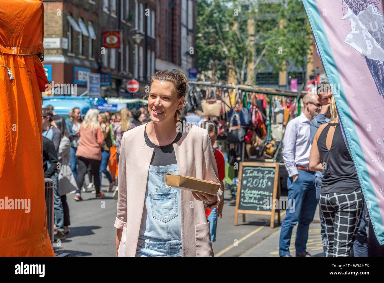 The open air and colourful street market at Leather Lane during a busy lunch hour - Stock Image