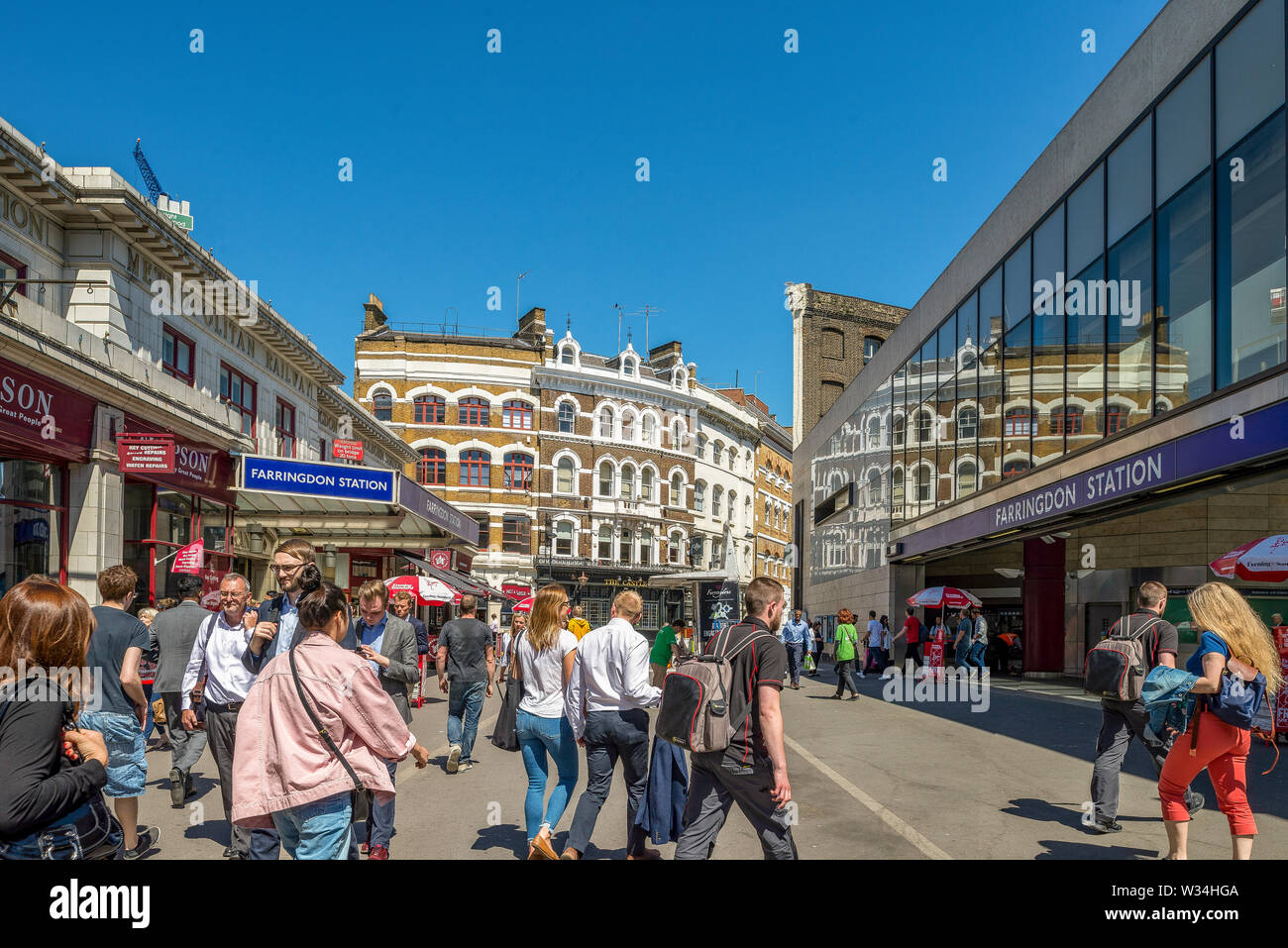 Farringdon Road busy with commuters and workers pouring out of Farringdon underground station on a sunny day - Stock Image