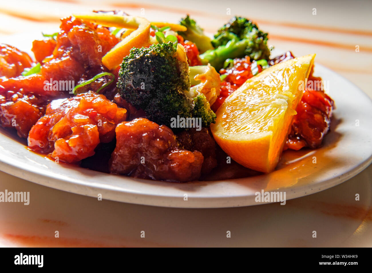 Hot and spicy chinese orange chicken with broccoli - Stock Image
