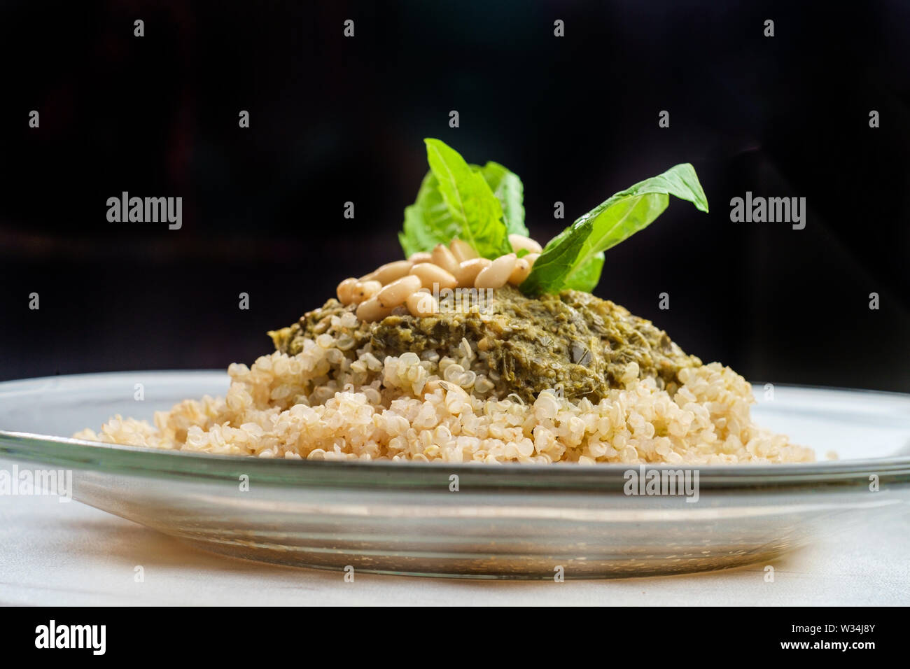 Healthy pesto quinoa salad with basil and pine nut garnish Stock Photo