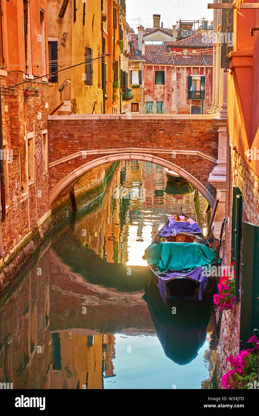 Canal with small bridge and moored gondola in Venice in the early evening, Italy - Stock Image