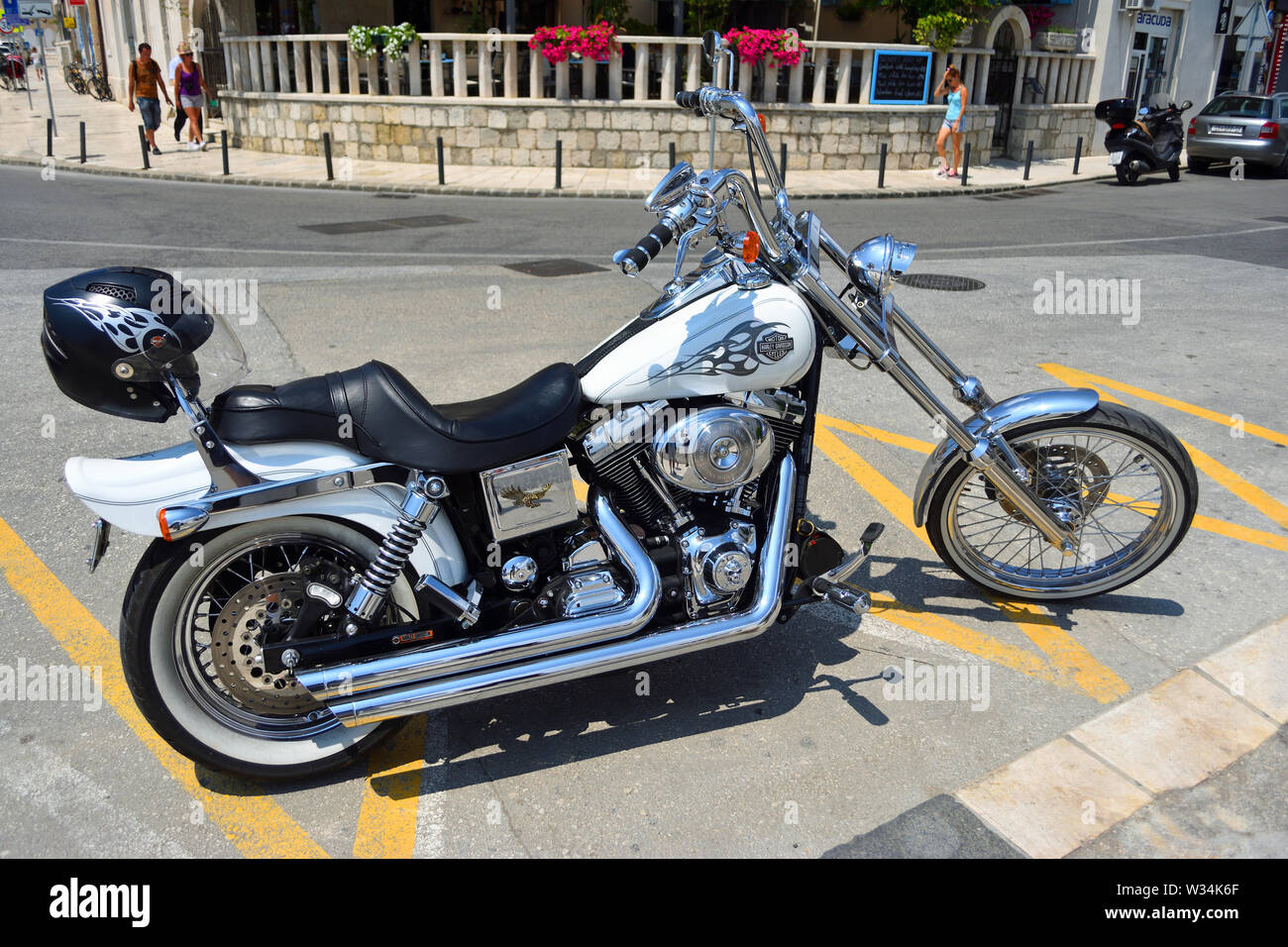 Harley Davidson Motorcycle parked in road with helmet on back. - Stock Image