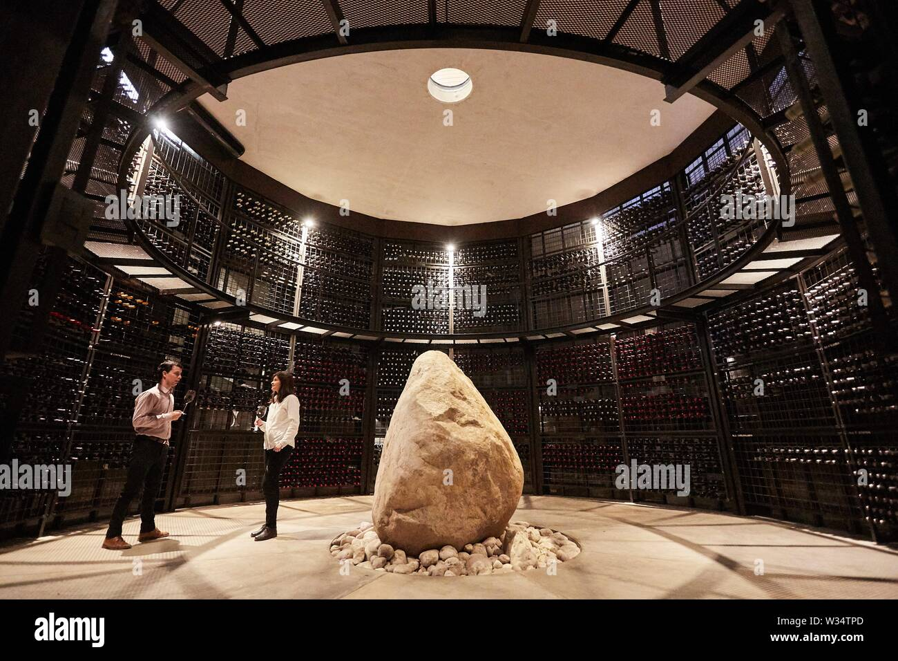 11 July 2019, Argentina, San Carlos: Two visitors drink wine surrounded by wine bottles in the wine cellar of Piedra Infinita wine. The Argentinian winery Piedra Infinita of the brand Zuccardi, was awarded by the World's Best Vineyards Academy as the best winery and winery in the world. This award recognizes the best 50 wineries in the world, based on the experience offered to the visitor. Photo: Marcelo Aguilar/dpa - Stock Image