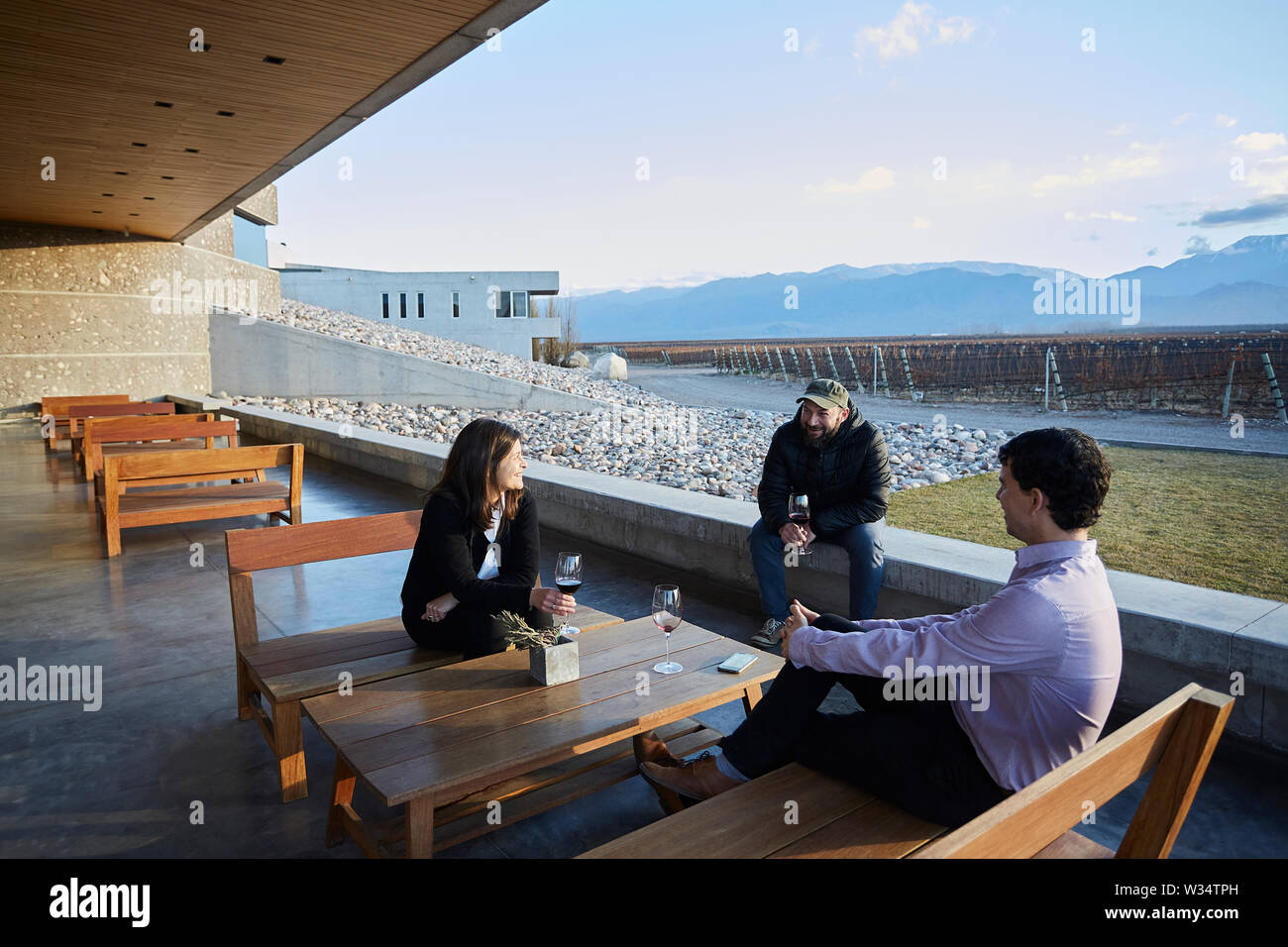 11 July 2019, Argentina, San Carlos: Visitors drink wine on a terrace next to the vineyards of Piedra Infinita. The Argentinian winery Piedra Infinita of the brand Zuccardi, was awarded by the World's Best Vineyards Academy as the best winery and winery in the world. This award recognizes the best 50 wineries in the world, based on the experience offered to the visitor. Photo: Marcelo Aguilar/dpa - Stock Image