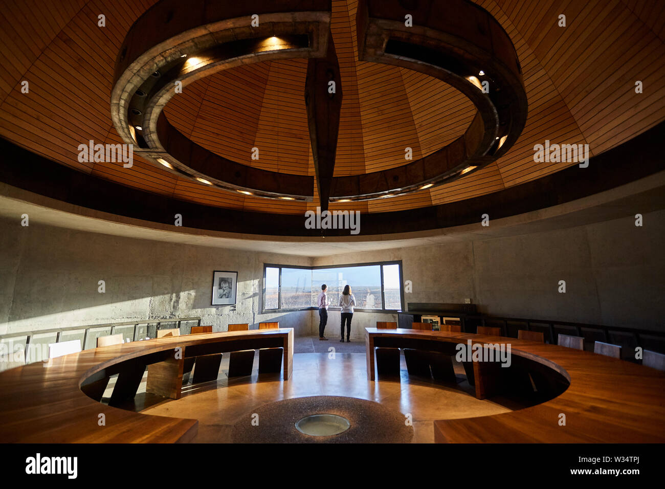 11 July 2019, Argentina, San Carlos: Two visitors look out of the window of a meeting room in the Piedra Infinita building. The Argentinian winery Piedra Infinita of the brand Zuccardi, was awarded by the World's Best Vineyards Academy as the best winery and winery in the world. This award recognizes the best 50 wineries in the world, based on the experience offered to the visitor. Photo: Marcelo Aguilar/dpa - Stock Image