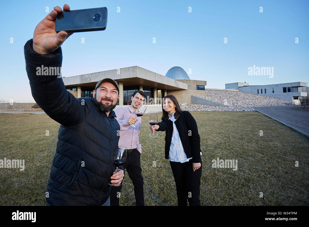 11 July 2019, Argentina, San Carlos: Visitors make a selfie with the building of Piedra Infinita in the background. The Argentinian winery Piedra Infinita of the brand Zuccardi, was awarded by the World's Best Vineyards Academy as the best winery and winery in the world. This award recognizes the best 50 wineries in the world, based on the experience offered to the visitor. Photo: Marcelo Aguilar/dpa - Stock Image