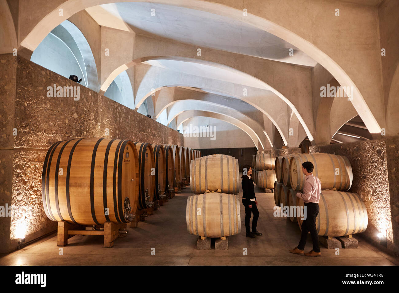 11 July 2019, Argentina, San Carlos: Two visitors stand in the wine cellar of Piedra Infinita. The Argentinian winery Piedra Infinita of the brand Zuccardi was awarded by the World's Best Vineyards Academy as the best winery and winery in the world. This award recognizes the best 50 wineries in the world, based on the experience offered to the visitor. Photo: Marcelo Aguilar/dpa - Stock Image