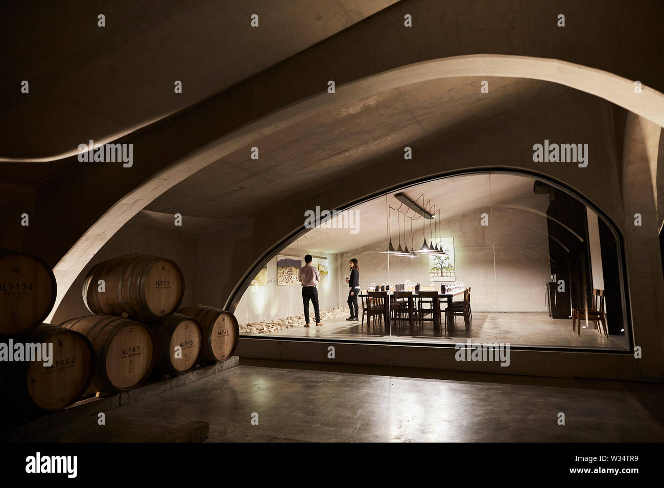 11 July 2019, Argentina, San Carlos: Two visitors drink in the wine cellar of Piedra Infinita. The Argentinian winery Piedra Infinita of the brand Zuccardi, was awarded by the World's Best Vineyards Academy as the best winery and winery in the world. This award recognizes the best 50 wineries in the world, based on the experience offered to the visitor. Photo: Marcelo Aguilar/dpa - Stock Image