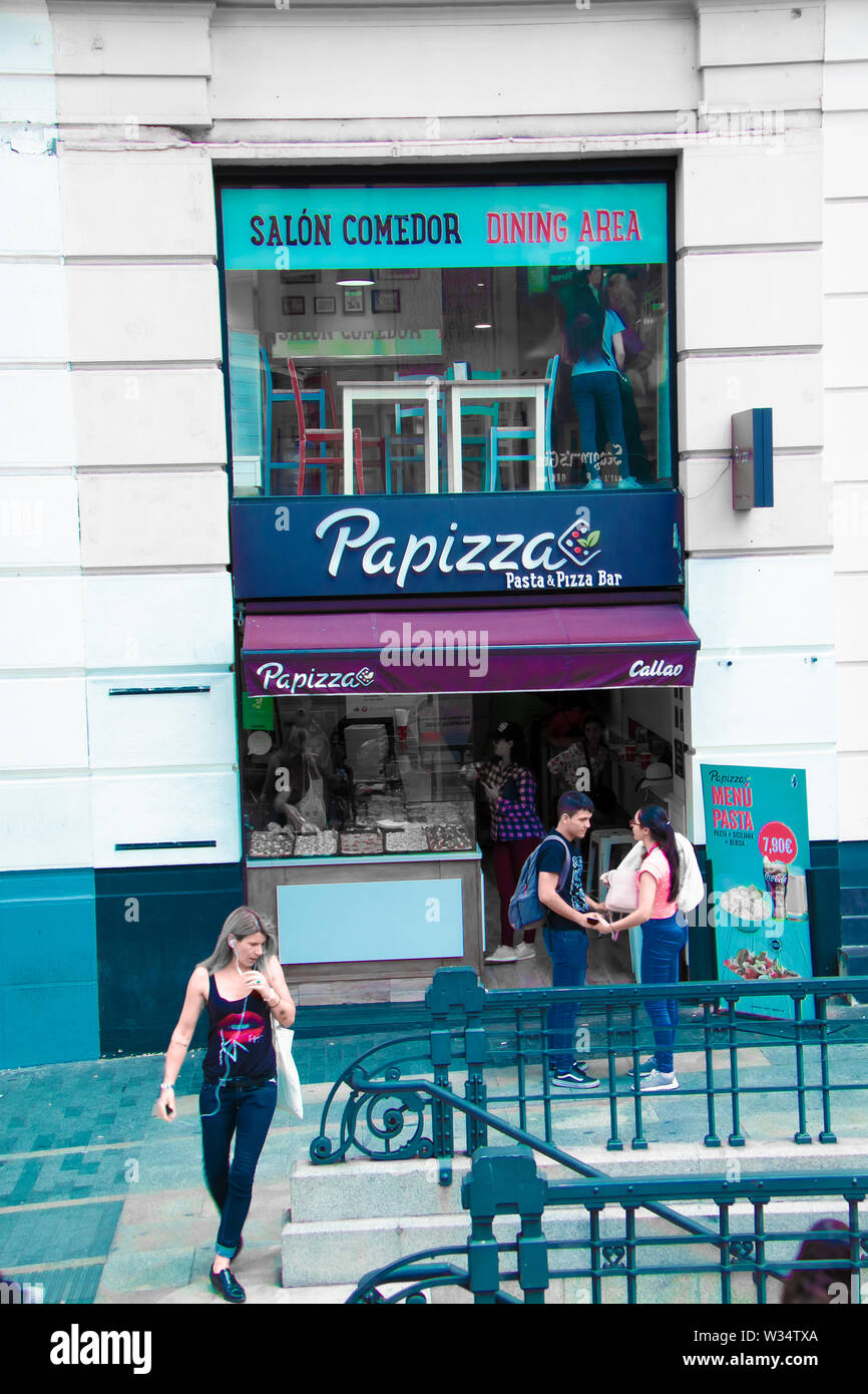Madrid, Spain - June 21, 2019: Young people next to a pizzeria on Gran Via avenue, in the center of Madrid Stock Photo