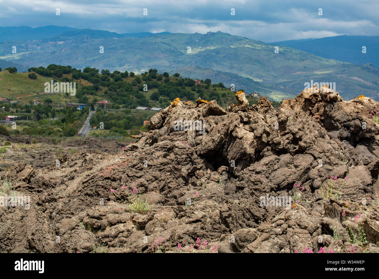 View on small village located just few meters from new eruption lava fields on slopes of Mount Etna volcano, National Park of Etna, Sicily island, Ita - Stock Image