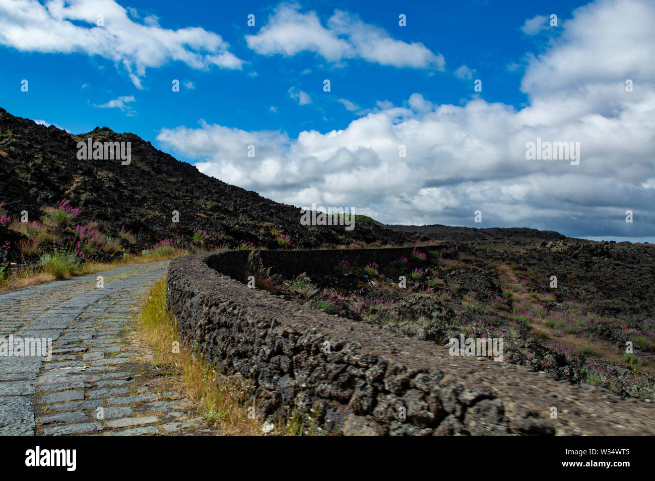 Stone road through black lava fields on slopes of Mount Etna volcano, car access to National Park of Etna, Sicily island, Italy, travel destination - Stock Image