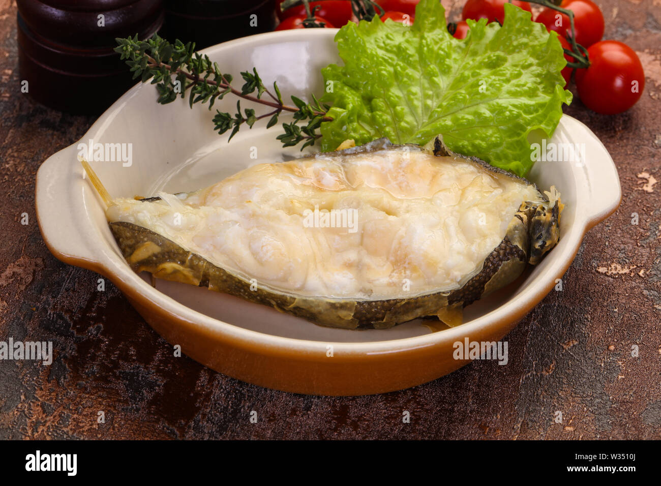 Baked wolffish steak with salad leaves - Stock Image
