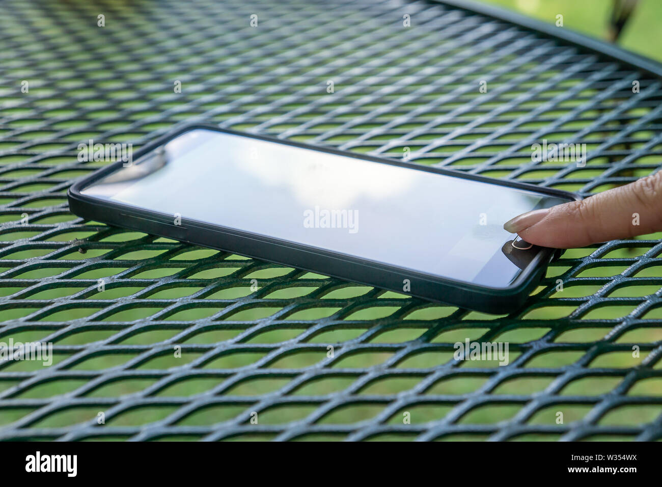 Person's finger tapping on touch button using smart cell phone. Modern tech outside resting on textured pattern outdoor patio table. Sun reflecting gl - Stock Image