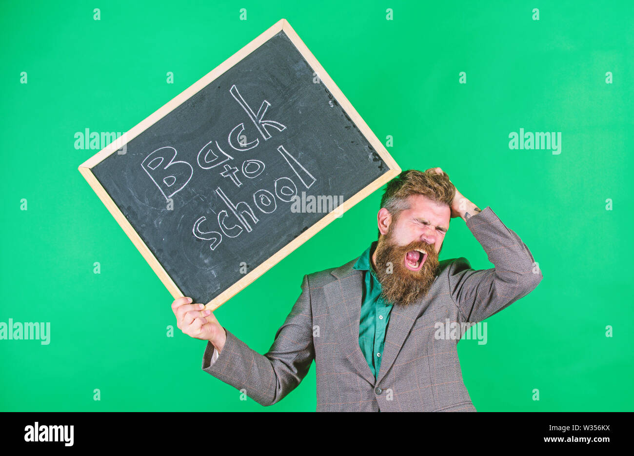 Teacher with tousled hair stressful about school year beginning. Teacher bearded man holds blackboard with inscription back to school green background. Keep working. Teaching stressful occupation. - Stock Image