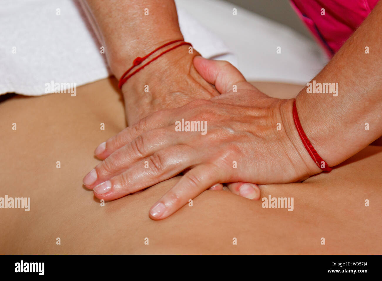 professional therapeutic massage of the back and neck. woman doctor massages girl athlete in a massage room. body and health care. procedure for recov - Stock Image