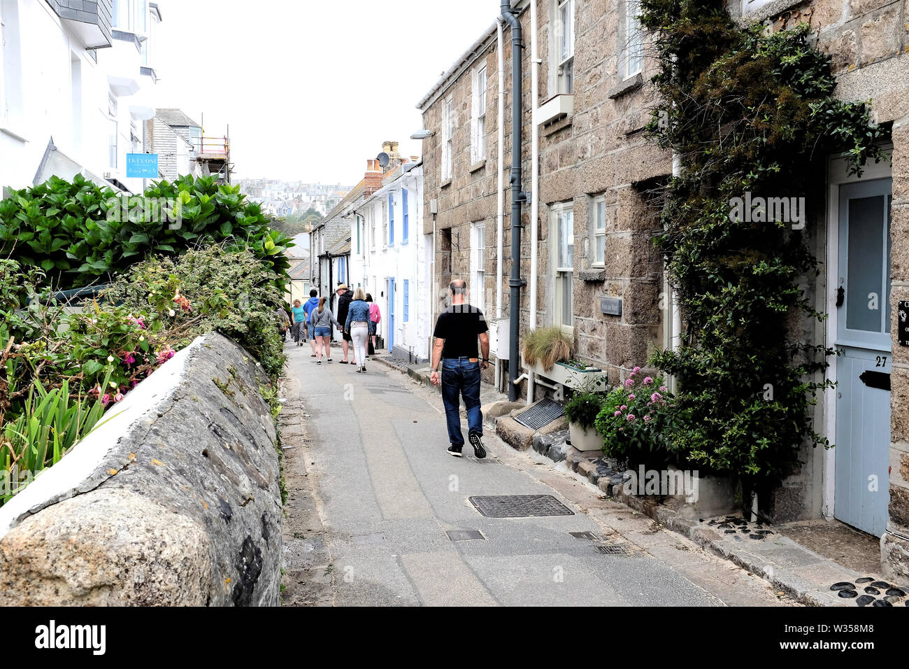 St. Ives, Cornwall, UK. June 29, 2019.  Holidaymakers walking the coast path down the Warren in The town of St. Ives in Cornwall, UK. - Stock Image