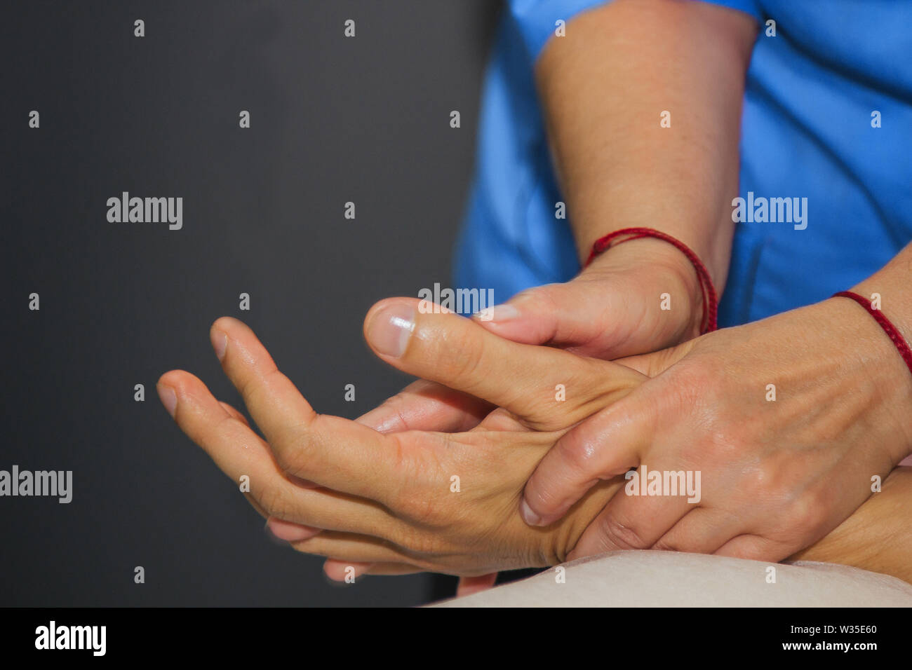 professional therapeutic massage of the hands and palms. woman doctor massages a man athlete in a massage room. body and health care. procedure for re - Stock Image