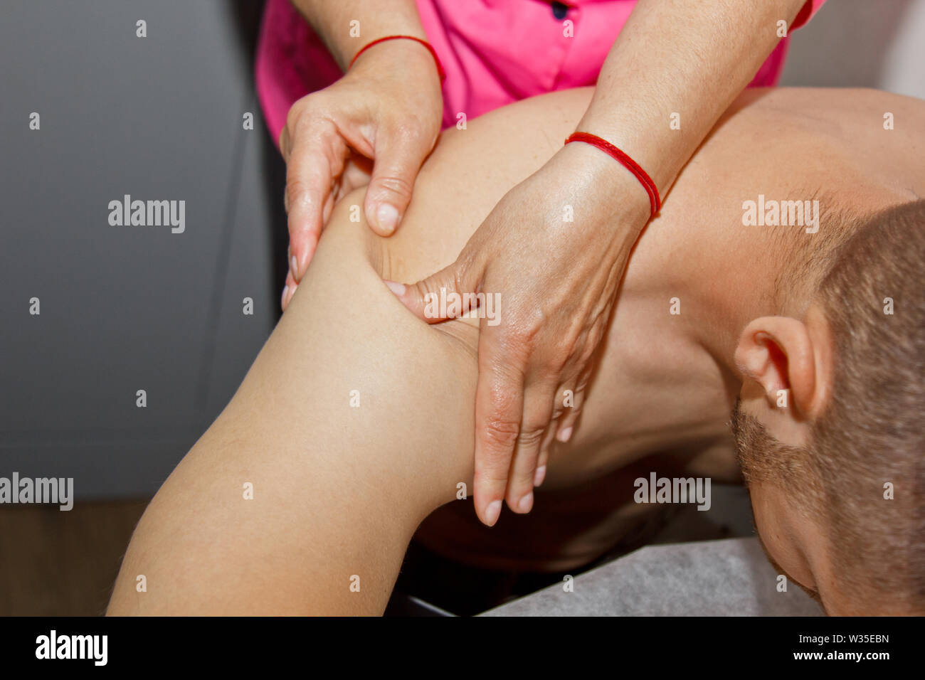 professional therapeutic shoulder and neck massage. woman doctor massages a man athlete in a massage room. body and health care. procedure for recover - Stock Image