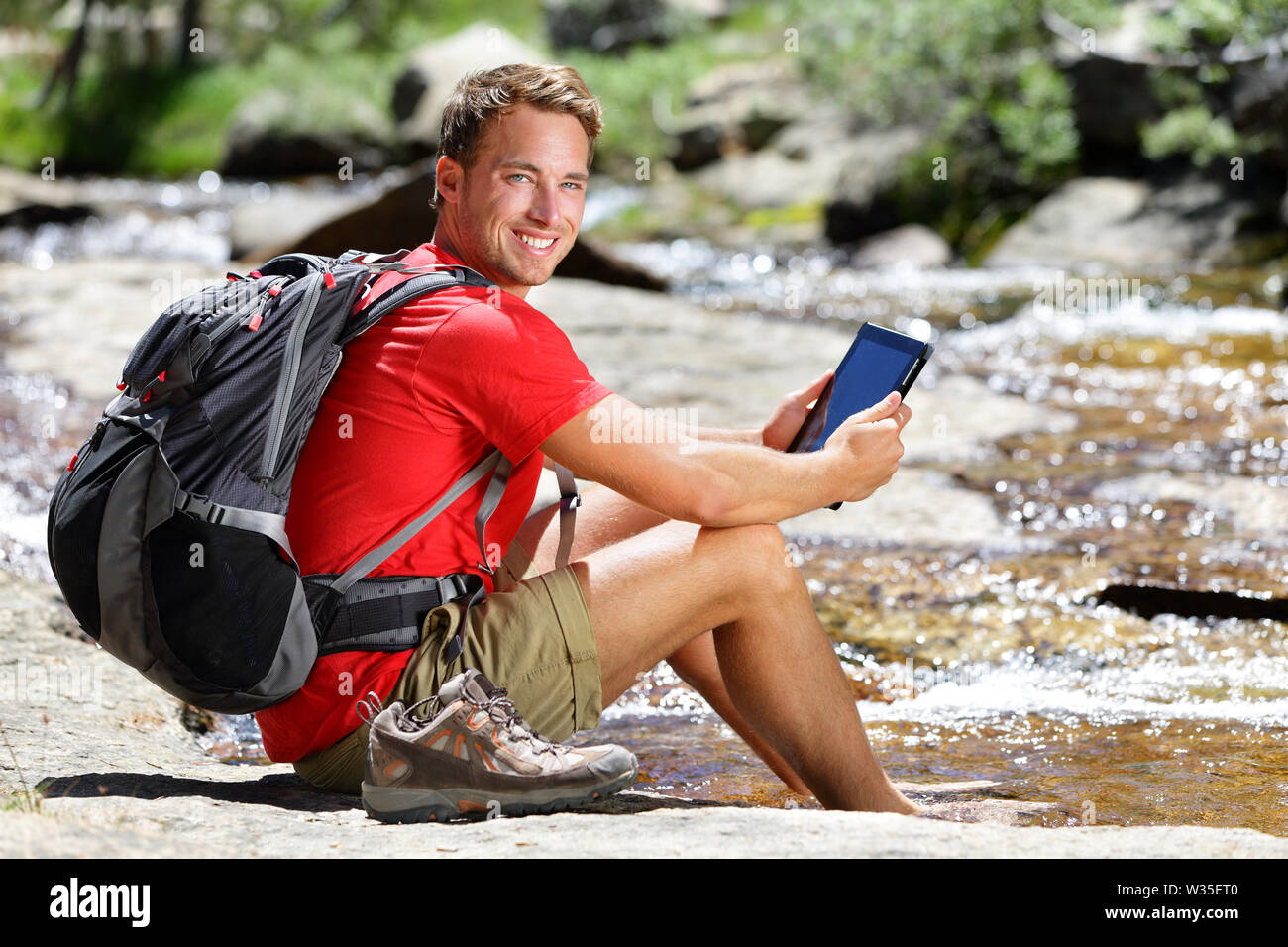 Tablet Computer Man Hiker Relaxing By River Holding Ebook Reader Reading E Book Or Map Hiking In Yosemite Usa Using Travel App Or Map During Hike Stock Photo Alamy