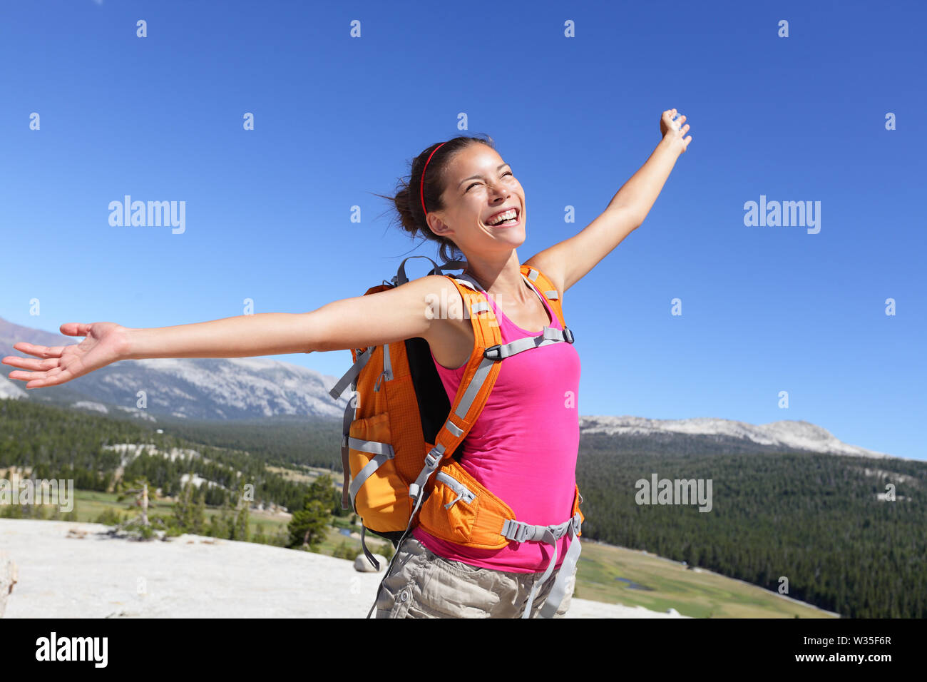 Happy hiker girl hiking carefree in nature. Young asian adult showing freedom pose after reaching summit mountain. - Stock Image