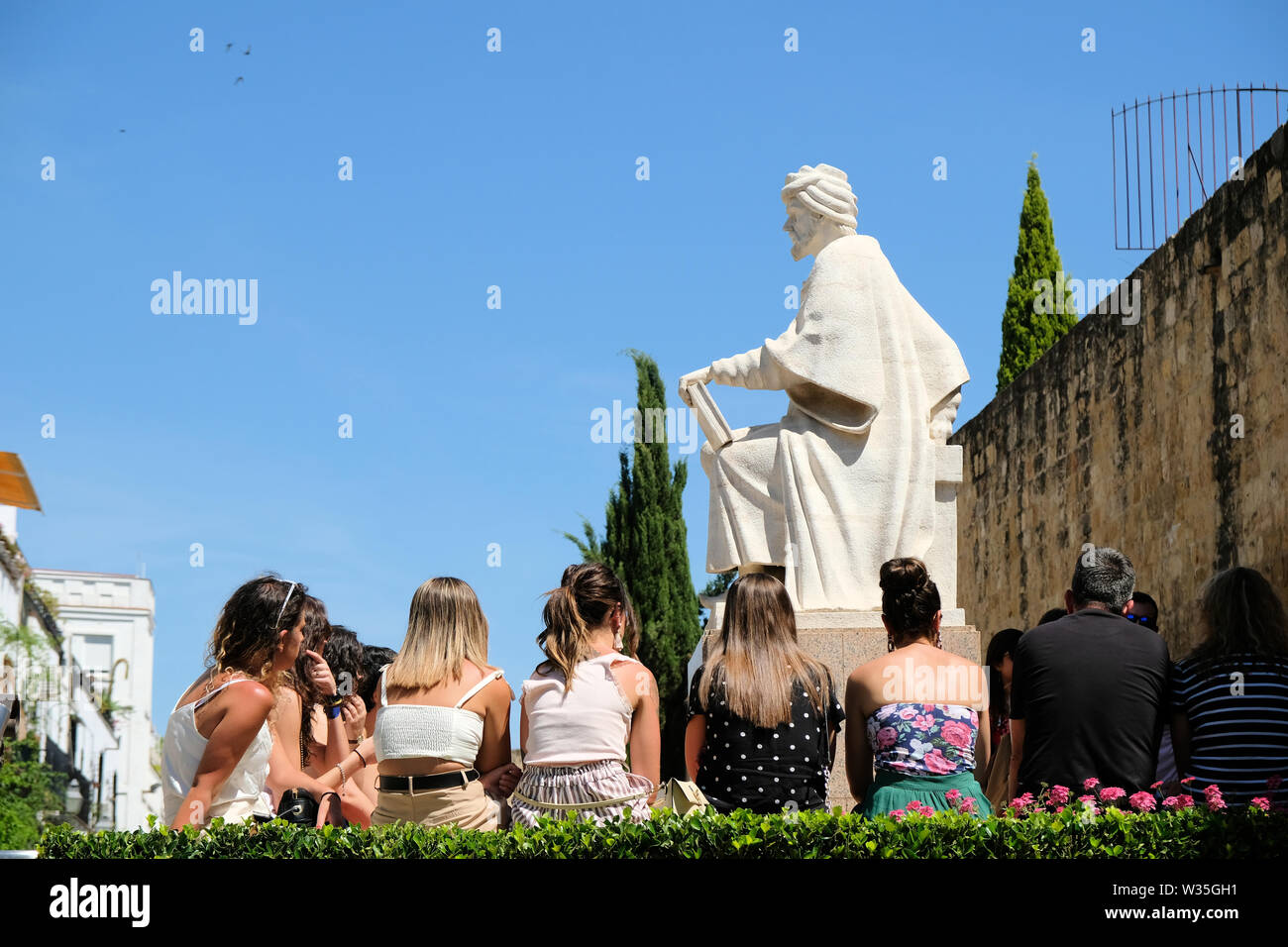 Statue of medieval philosopher Averroes in Cordoba, Spain, with modern students at the base of the statue as if in class listening to him teach. - Stock Image